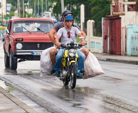 classic santa: Santa Clara, Cuba transportation unsafe practices: People using motorcycle to carry bulk goods on a rainy day while an old American classic car runs as a taxi in Santa Clara, Cuba.
