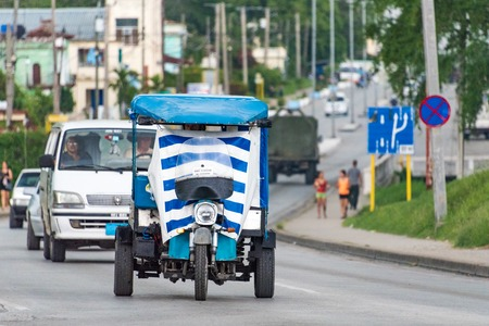 auto rickshaw: Transportation in Cuba: Three wheeled auto rickshaw or moto taxi carrying passengers on the streets of Santa Clara. They use plastic sheet as windcheaters for protection from rain.  The auto rickshaw is a common form of urban transport as taxi in Cuba pro