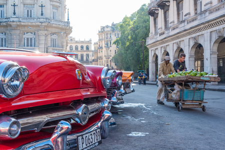 everyday scenes: Cuba tourism: old vintage classic American cars in Havana and the Cuban everyday lifestyle. People pushing a fruit and vegetables cart to sell in the vecinity.  Cuba transportation scenes are a major tourist attraction. Having a great collection of vintag