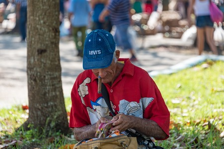 senior smoking: Sunday free market scenes, Santa Clara, Cuba: Senior man counting money while smoking a cigar, sitting under a tree.  The Sunday free market is a great success and offers a variety of products to buy at cheaper prices due to higher competition Editorial