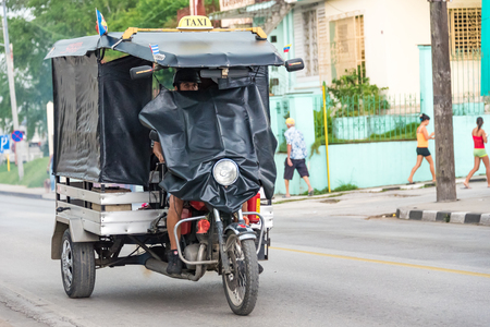 auto rickshaw: Cuba local transportation: Three wheeled auto rickshaw or moto taxi carrying passengers on the streets of Santa Clara. They use plastic sheet as windcheaters for protection from rain.  The auto rickshaw is a common form of urban transport as taxi in Cuba  Editorial