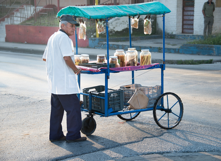 push cart: Cuban Senior selling snacks on a push cart on the streets of Santa Clara. Operating push cart is one of the authorized jobs for self-employment in Cuba.