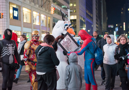 new york city times square: Buskers in Times Square at night in New York City : Times Square is a major commercial intersection and neighborhood in Midtown Manhattan.The landmark is brightly adorned with billboards and advertisements.  Times Square is sometimes referred to as The Cr