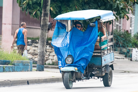 auto rickshaw: Cuba transportation: Three wheeled auto rickshaw or moto taxi carrying passengers on the streets of Santa Clara. They use plastic sheet as windcheaters for protection from rain.  The auto rickshaw is a common form of urban transport as taxi in Cuba provid Editorial