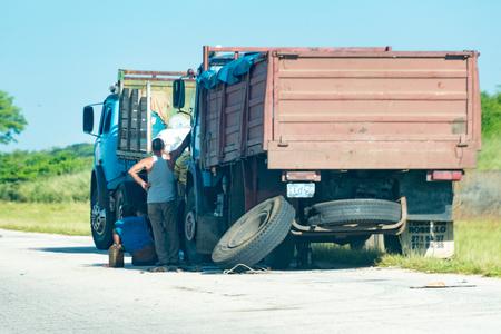 broken down: Cuba National Highway scenes: Broken down truck on highway being repaired with help from another truck.