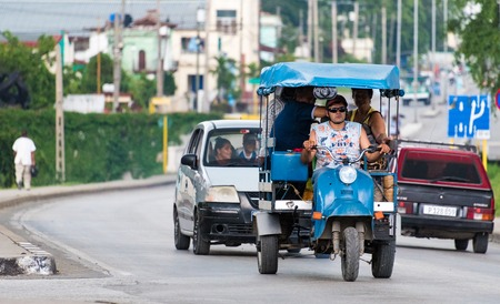 auto rickshaw: Cuba local Transportation: Three wheeled auto rickshaw or moto taxi carrying passengers on the streets of Santa Clara.  The auto rickshaw is a common form of urban transport as taxi in Cuba providing cheap means of moving goods and people within the city.