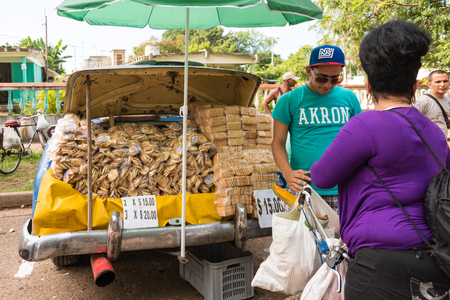 produced: Sunday free market, Santa Clara: Privately produced crackers in the trunk of an old car being sold at the Sunday market in Sandino area of Santa Clara, Cuba.  The Sunday free market is a great success and offers a variety of products to buy at cheap price