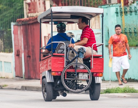 auto rickshaw: Transportation in Cuba: Three wheeled auto rickshaw or moto taxi carrying a passenger and his bicycle in Santa Clara.  The auto rickshaw is a common form of urban transport as taxi in Cuba providing cheap means of moving goods and people within the city.