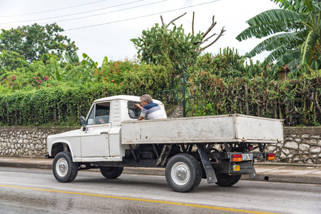 means of transportation: Santa Clara, Cuba transportation unsafe practices: Man travelling in pickup truck on a rainy day in Santa Clara, Cuba.  Cubans use various means of transport for local commutation including carpooling and hitchhiking and try to save as much money as possi