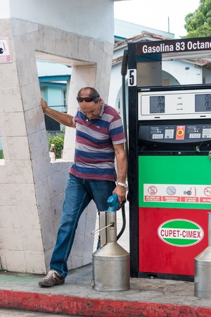 Santa Clara gasolina station: Man filling gasoline in container at a filling station run by Cupet-Cimex in Santa Clara, Cuba.  Cupet is Cubas state oil company. Cupet along with Cimex operates a chain of filling stations selling gasoline in Cuba. Cimex o Editorial