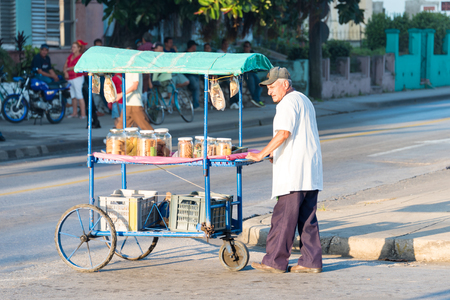 Cuban Senior selling snacks on a push cart on the streets of Santa Clara. Operating push cart is one of the authorized jobs for self-employment in Cuba.