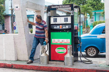 Gas station in Santa Clara: Man filling gasoline in container at a filling station run by Cupet-Cimex in Santa Clara, Cuba.  Cupet is Cubas state oil company. Cupet along with Cimex operates a chain of filling stations selling gasoline in Cuba. Cimex or