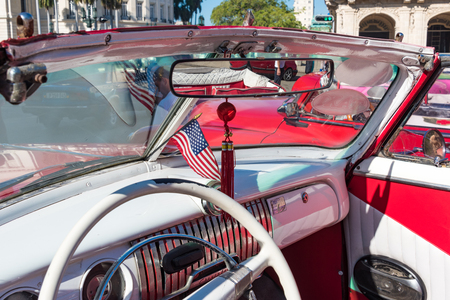 everyday scenes: Cuba tourism: old vintage classic American cars in Havana and the Cuban everyday lifestyle. The US flag is more and more common in the Caribbean Island.  Cuba transportation scenes are a major tourist attraction. Having a great collection of vintage cars, Editorial