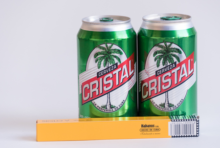 cristal: Products made in Cuba: Cohiba cigar and Cristal beer cans together showing the most popular brands in their product category.  Cristal brand is the most popular beer in Cuba with  low alcohol content of 4.9%. Cohiba is a brand of premium cigar produced in Editorial