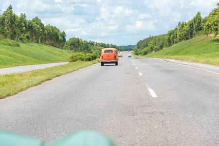 Cuba transport: Old vintage cars in the National Highway travelling at an approximate 100kmh.  Due to the lack of imports Cubans have become experts at innovating and keeping obsolete cars working.