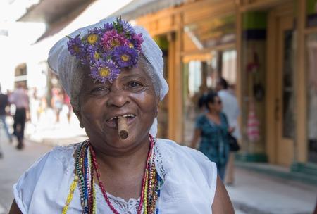 mujeres morenas: pueblo cubano Afro Caribe: mujer vestida con la ropa y los accesorios religiosa afro muy común en la Habana Vieja. La Habana Vieja es un Patrimonio de la Unesco y un importante punto de referencia turística en la isla del Caribe. Editorial