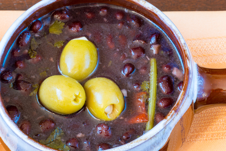 beans soup: Cuban cuisine: black beans soup served in a clay pot and garnished with three green olives. Stock Photo