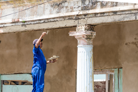 pinar: Cuban bricklayer repairing a classic vintage colonial building in Pinar del Rio,Cuba Recovering the old architecture in Cuba has priority in the government plans. Those beautiful buildings are an attraction to tourists.