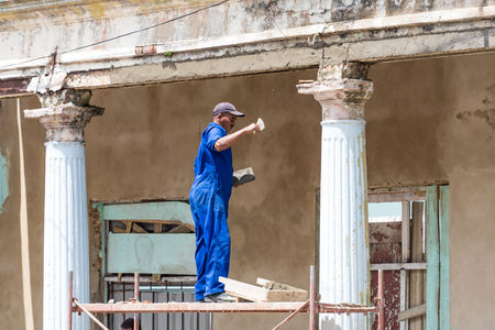 Cuban bricklayer repairing a classic vintage colonial building in Pinar del Rio,Cuba Recovering the old architecture in Cuba has priority in the government plans. Those beautiful buildings are an attraction to tourists.