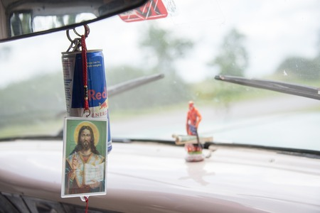 pesos: Saint Lazarus in dashboard of old American car in Cuba. The car works as taxi between Pinar del Rio and Havana. There is a five pesos bill and an USD dollar in the Saint feet.
