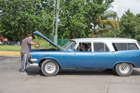 Man refilling the radiator of an old American car working as taxi between Havana and Pinar del Rio, Cuba The lack of imports have forced Cubans to maintain old cars from the 50s running. Nowadays, they are the source of private transportation taxis. While