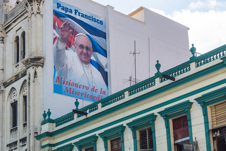 everyday: Pope Francis poster in the Popularly known as Reina Church, the Parish of the Sacred Heart of Jesus and St. Ignatius of Loyola is one of the most beautiful Catholic temples in Cuba. Exterior details and the everyday life in the Cuban capital days before t