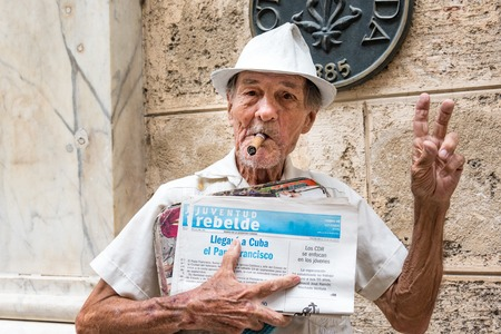 senior smoking: Cuban old senior citizen selling a Juventud Rebelde newspaper in Old Havana a day before the arrival of Pope Francis to the Island. He is smoking a Cuban cigar and wearing a hat. Editorial
