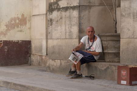 needy: Old needy man selling newspapers in Old Havana,Cuba. Newspapers are often bought by tourists as souvenirs of one of the last communist countries in the world with no freedom of expression. Editorial