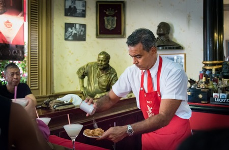 hemingway: Floridita, Havana,Cuba. Interior views, the bar specializing in Daiquiri cocktail is a major tourist attraction landmark in the city. Putting salt in a green banana chips plate inside El Floridita bar