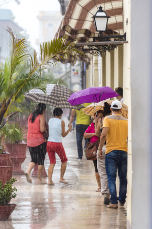 everyday people: Rainy day in Sancti Spiritus, Cuba:  Cubans everyday way of life during a rainy tropical day in the Caribbean Island. People braving the rain in the citys Boulevard