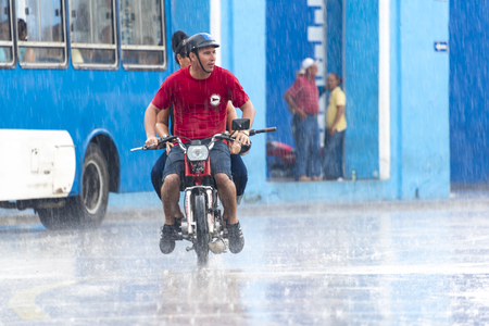 everyday: Rainy day in Sancti Spiritus, Cuba:  Cubans everyday way of life during a rainy tropical day in the Caribbean Island. Couple braving the rain in a small motorcycle in the Historic District