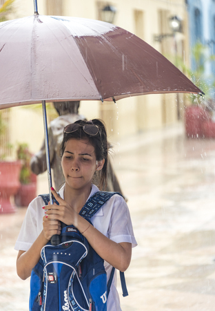 everyday: Rainy day in Sancti Spiritus, Cuba:  Cubans everyday way of life during a rainy tropical day in the Caribbean Island. Medicine student in the citys boulevard Editorial