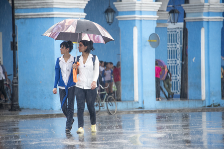 everyday: Rainy day in Sancti Spiritus, Cuba:  Cubans everyday way of life during a rainy tropical day in the Caribbean Island. Medicine students in the Historic District