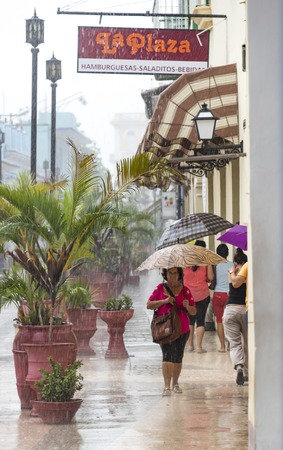 everyday: Rainy day in Sancti Spiritus, Cuba:  Cubans everyday way of life during a rainy tropical day in the Caribbean Island. People braving the rain in the citys Boulevard