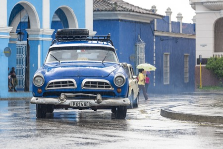 everyday: Rainy day in Sancti Spiritus, Cuba:  Cubans everyday way of life during a rainy tropical day in the Caribbean Island. Obsolete American car in the Historic District