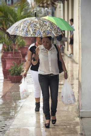 Rainy day in Sancti Spiritus, Cuba:  Cubans everyday way of life during a rainy tropical day in the Caribbean Island. People in the citys Boulevard close to the Historic District