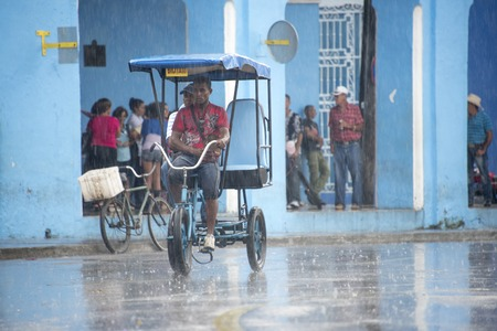 everyday: Rainy day in Sancti Spiritus, Cuba:  Cubans everyday way of life during a rainy tropical day in the Caribbean Island. Rickshaw or Bicitaxi in the Historic District Editorial