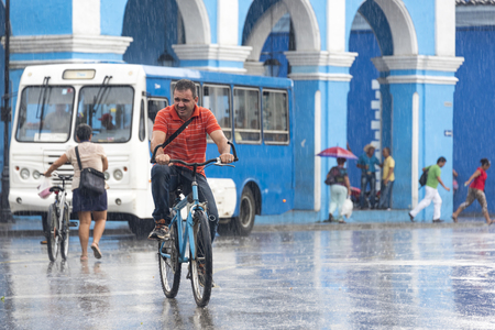 everyday people: Rainy day in Sancti Spiritus, Cuba:  Cubans everyday way of life during a rainy tropical day in the Caribbean Island. People in bicycles in the Historic District