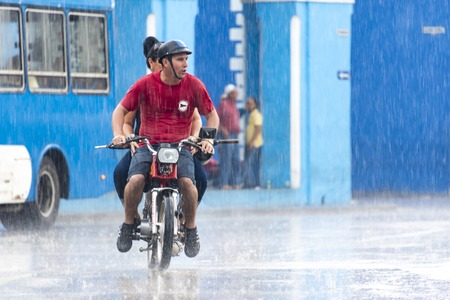 Rainy day in Sancti Spiritus, Cuba:  Cubans everyday way of life during a rainy tropical day in the Caribbean Island. Couple braving the rain in a small motorcycle in the Historic District
