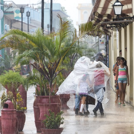 everyday: Rainy day in Sancti Spiritus, Cuba:  Cubans everyday way of life during a rainy tropical day in the Caribbean Island. People in the citys Boulevard close to the Historic District
