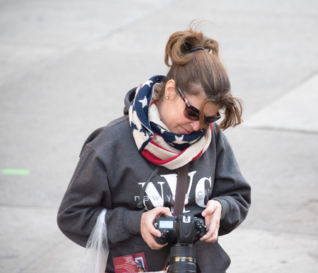 historic district: Tourist photographer enjoying her New York City sightseeing in the Historic District. She wears U.S flag scarf and a N.Y.C hoodie