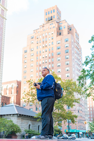 historic district: Tourist photographer in vantage point scouting the view before taking some pictures. He is in the Historic district which is a great landmark for architectural photography. Editorial