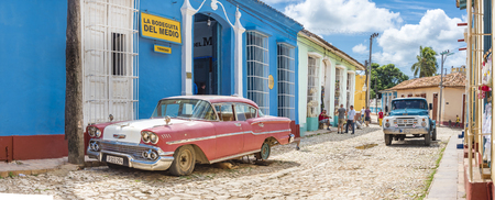 world heritage site: La Bodeguita del Medio in Trinidad,Cuba. The landmark is a popular bar and restaurant in the Unesco World Heritage Site. It features an Old American Car parked in the cobblestone street