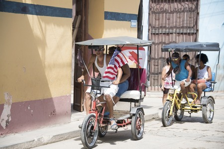 traction: Cuban rickshaw or bicitaxi with U.S.A and Canadian flags in Trinidad,Cuba. The rickshaw is used as a human traction taxi serving the towns population and tourists. After the closer relations between Cuba and the U.S, American flags are common in the Cari