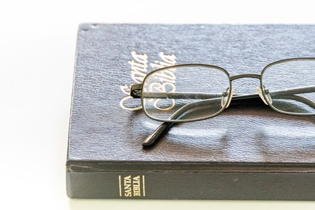 scriptures: Holy Bible book with reading glasses on white background.The Christian scriptures, consisting of the Old and New Testaments.