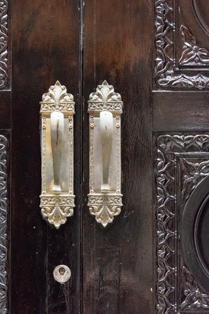 architectural feature: Metal handles on a vintage,old,brown, wooden,colonial door. The architectural feature is beautifully carved. Spanish colonial architecture can be seen in Old Havana which is a Unesco World Heritage Site. Stock Photo