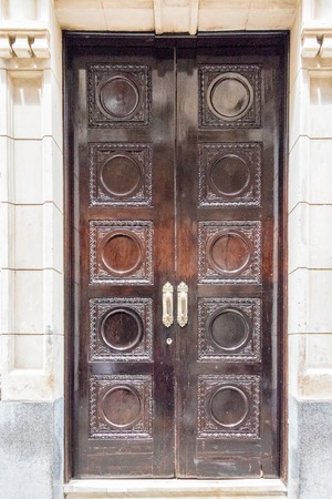 building feature: Large closed big brown doors in a colonial building. The building feature is carved and has polished handles. Detail of  Spanish architecture tourists can see in Old Havana