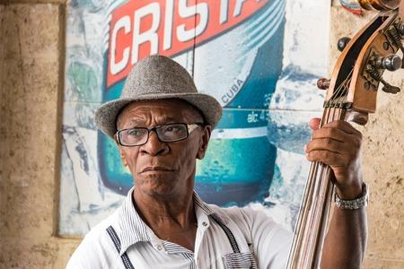 barra: Anciano hombre cubano que juega el bajo ac�stico en un bar tur�stico. Lleva un sombrero y hay un cartel Cristal en el fondo. m�sica y bebidas cubana son muy populares entre los visitantes de la isla del Caribe.