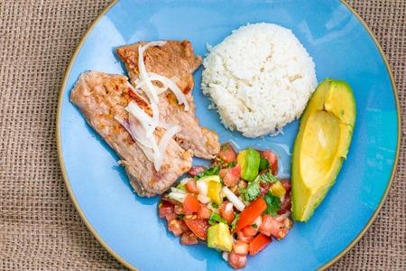 latin american: Latin American cuisine fusion: pork steak, white rice,pico de gallo and avocado.Mexican and Cuban cuisine fusion produces a healthy balanced plate of food