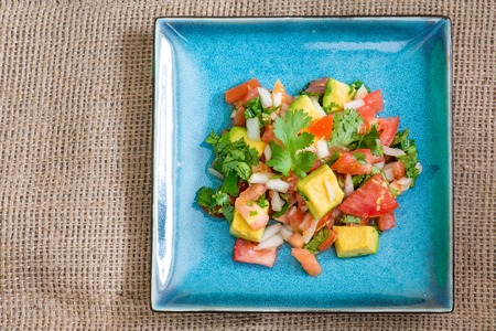 Mexican cuisine: Pico de Gallo.  The dish  is a fresh, uncooked salad made from chopped tomato, onion, cilantro, fresh serranos, salt, and key lime juice. Other ingredients may also be added.
